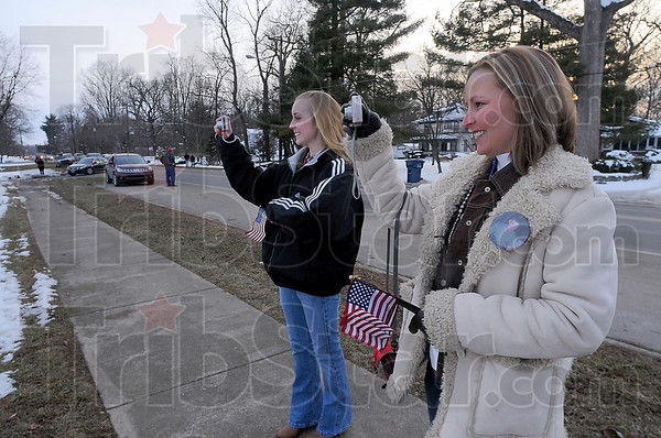 Recording the return: Jessi Kirkham and Becky Young take photographs of the banners hung from the front fence at the Marine Reserve Center on Fruitridge Avenue. Young was waiting for the return of her husband Sgt. Cody Young and Kirkham greeted Lance Corporal Nick Green.