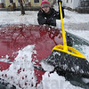 Clean sweep: Kaitlen Long sweeps the heavy, wet snow from her car parked along south 7th street Friday afternoon. While she wasn't leaving just then, her parents encouraged her to keep the snow off.
