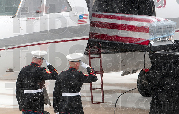 Tribune-Star/Joseph C. Garza<br /> Honoring a fellow warrior: A pair of Marines salute as the casket of the late Cpl. Gregory Stultz is loaded off a charter plane Wednesday at the Terre Haute International Airport-Hulman Field.