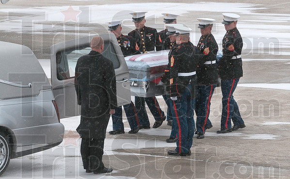 Tribune-Star/Joseph C. Garza<br /> Military honors: A Marine Corps honor guard carries the casket of the late Marine Cpl. Gregory Stultz to a French Funeral Home hearse after the casket's arrival at the Terre Haute International Airport-Hulman Field on Wednesday.