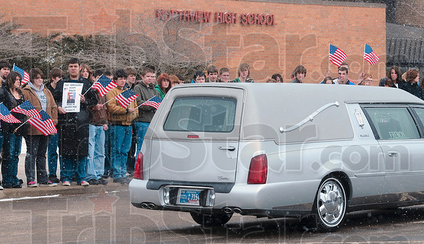 Tribune-Star/Joseph C. Garza<br /> Honoring a former Knight: A Northview High School student holds a photo of the late Marine Cpl. Gregory Stultz as the hearse carrying Stultz's casket passes by the 2006 graduate's alma mater Wednesday outside of Brazil.