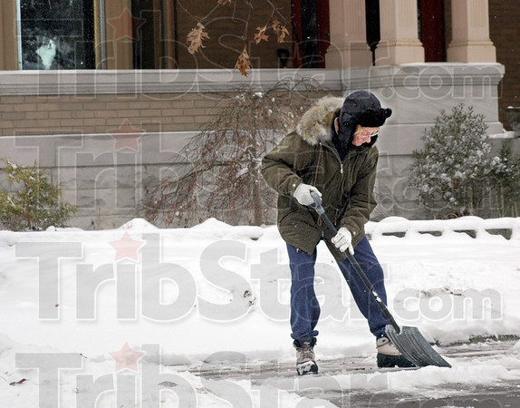 """Snow job: Eighty-three-year-old Willie Viertel Grissom removes snow from the sidewalk in front of her south Sixth Street home Tuesday afternoon. Watching her work form his perch inside her home is her cat """"Spotsey."""""""