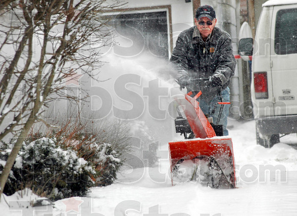 Snow blower: Buck Hudson uses a snowblower to remove snow from the driveway of his south 20th Street home Tuesday afternoon.