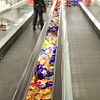 On the conveyor - in between you have impulse purchase items... chips, candies, sometimes if it's cold; winter socks... it's slow enough to give things a once over and put them back if you don't know what it is.