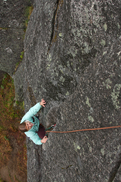 Looking down on Tracy as she works her way up pitch one of <i>The Slot 5.7</i> on the Monolith in Archangel Valley.