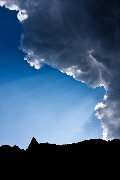 Afternoon sunbeams break over a lone cloud to illuminate Pinnacle Peak above Archangel Valley.
