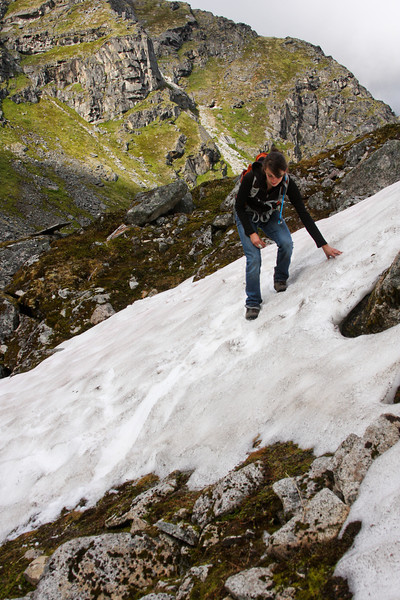 Rachel follows across a sloped snowpatch in a hanging valley overlooking a lake.