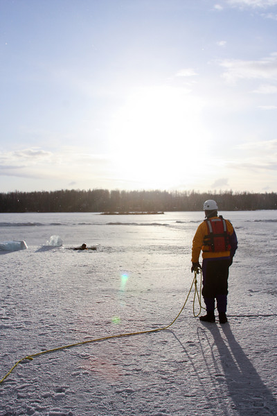 A drill is about to begin, with one victim through the ice and a rescuer geared up and ready to assist.
