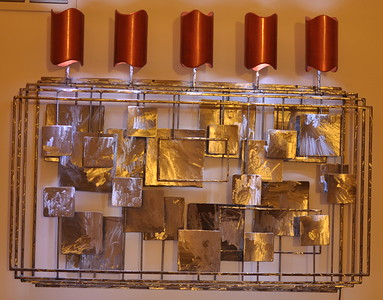 Lights are made from PVC sewer pipe (with Copper acrylic finish), with LED light pucks shining cold light up the wall, and also down through the mosaic steel.