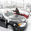 Optimist: Kash Ahmadi uses a special tool to clean the snow from the cars on his Auto House Superstore lot at US 41 and College Avenue.