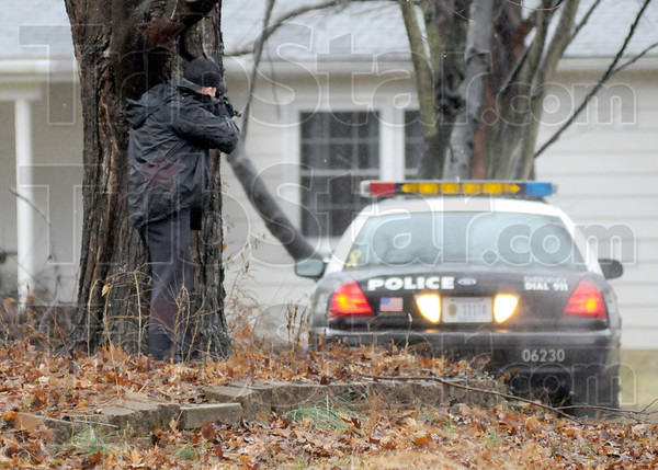 Scoped: Acting Terre Haute chief of police Marc Eldred looks through the scope on his rifle attempting to see a suspect inside a home in Terra Vista Thursday afternoon.