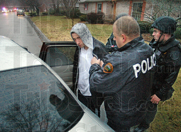 Gotcha: Terre Haute police officers put the suspect in a squad car after taking him into custody from a house in Terra Vista Thursday afternoon. The suspect lead police on a chase and fired shots at the officers during the event.