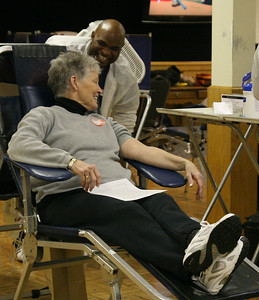 A blood donor laughs with an American Red Cross worker before donating blood.