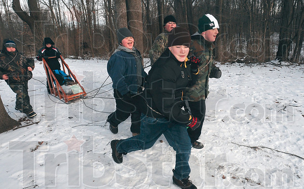 Tribune-Star/Joseph C. Garza<br /> Klondike competitors: Boy Scout Jacob Wheatley, center, glances behind himself as he runs with his fellow Troop 434 members as they pull their team's supply sled Saturday during the Klondike Derby at Camp Wildwood. With Wheatley are, from left, Jarrett Hendrix, Mark Olinske, in sled, Jared Bryant, Jacob Bryant and Tony Eley.
