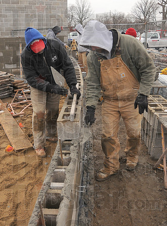 Work goes on: Bricklayers Kevin Russell and Jason Helton work together to construct a wall for the athletic facilities at Memorial Stadium Monday afternoon. They said they'd prefer to be working in 75 degree, sunny weather where the mortar is easier to work with.