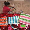 Take you pick: Elly Williams creates purses on her bedroom floor after school Tuesday. She is donating half the proceeds from the sales of her craft to help with disaster relief in Haiti.