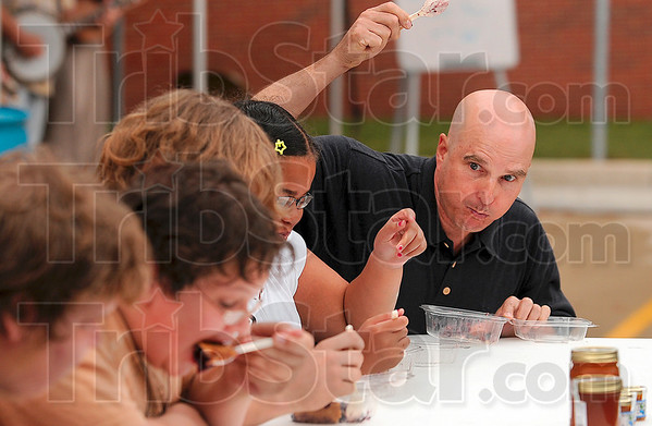 Blueberry pie eating contest participant Bill Carper raises his hand first to signify he is finished during the contest Thursday at the Blueberry Festival at Central Presbyterian Church. Carper won the contest.