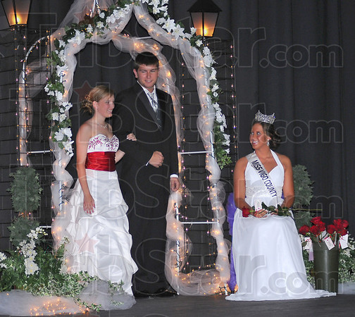 Evening gowns: Davetta Cox is escorted by Ridgley Smith for the evening gown competition portion of the Vigo County Fair Queen pageant Thursday evening. Outgoing 2009 queen Mary Roberts is at the right.