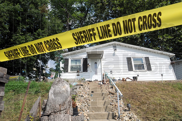 Homicide scene: Crime scene tape and a deputy sheriff keep the house at 7155 Robertson Road secure until the investigation into the shooting death of Al Kiger is complete.