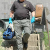 Investigator: Crime Scene Investigator John Moats leaves the home on Robertson Road owned by Al Kiger Thursday morning. Kiger was shot to death early Thursday morning.