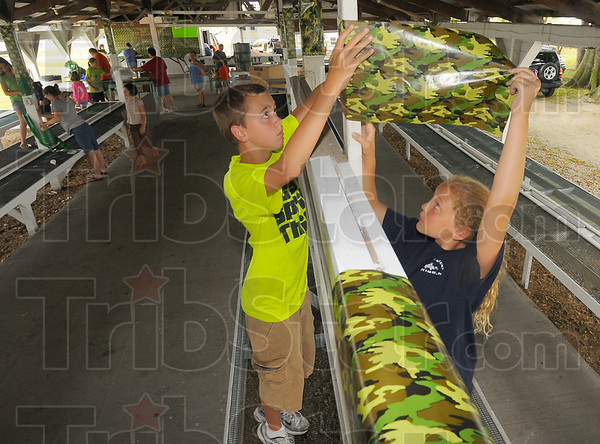 Teamwork: Jacob Weir and his sister Morgan work together to decorate the Rabbit Barn for the upcoming Vigo County Fair.