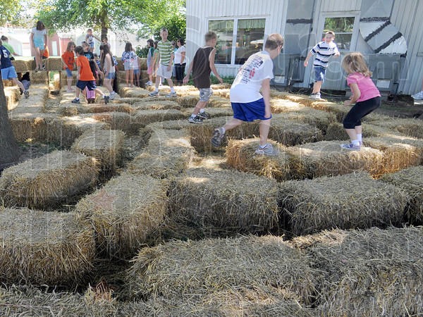 Tribune-Star file photo/Bob Poynter<br /> A maze....ing: A group of kids navigate the maze of straw bales just outside the 4-H Rabbit judging area Monday morning at the fairgrounds.