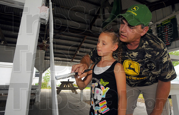 Getting ready: Thursday was the day to get the Rabbit Barn at the Wabash Valley Fairgrounds ready for the Vigo County Fair. Here Kaitlin Burns gets instruction in painting from her dad Steve.