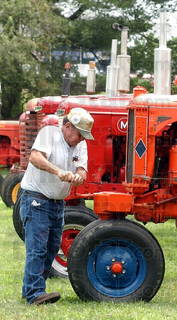 Start your engines: Fred Hartmann cranks the engine on his 1935 Allis Chalmers UC tractor, getting it started to ride in the Antique Tractor Parade of Power at the Vigo County Fair Sunday afternoon.