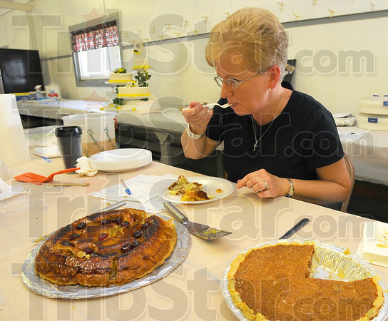 Someone has to do it: Sandra Small takes a bite of pineapple upside-down pie as she judges the pies entries Sunday afternoon in the Open Class of the Vigo County Fair.