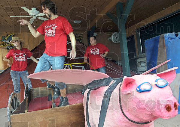 When pigs fly: The Red Bull Barn2Fly team prepares their display at Charlie's Sunday afternoon. The members are from left Kim Yates, Greg Otto and Clint Bright.