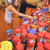 Helping hands: Memorial Uniter Methodist Church youth Jordan Cresgy, Mallory Metheny and Chase Cresgy stack jars of peanut butter that have been donated through the churchs' Peanut Butter Buddy effort. Some 2,000 jars of smooth as well as crunchy peanut butter will find their way to Haiti.