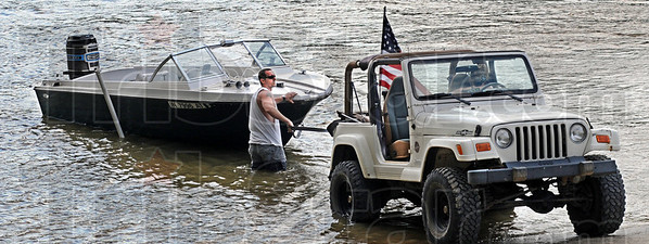 Patriotic pullout: Charles Roach give instructions to Brandi Larson as they prepare to remove their boat from the Wabash River in Fairbanks Park Sunday afternoon. The couple took about a three hour cruise.