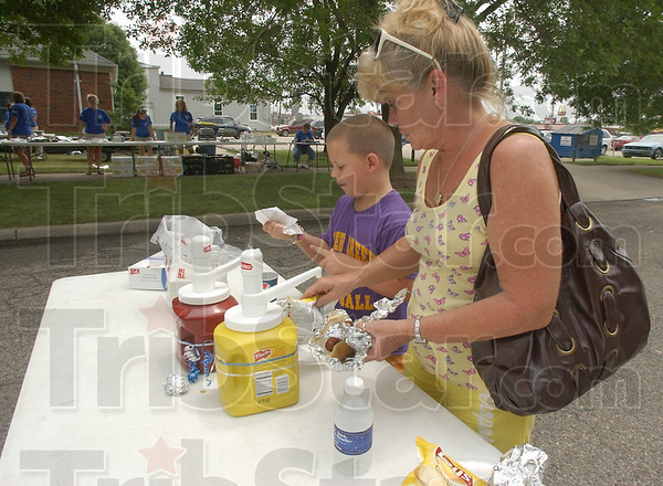 Party time: Payton Delicio and his grandmother Sondra Cagle dress their hot dogs at the block party sponsored by the law firm of Fleschner Stark Tanoos and Newlin. Proceeds from the party went to the United Way. Over $1,100 was raised during the event.