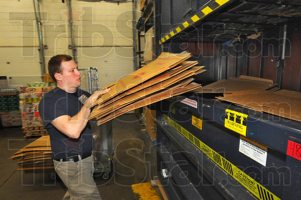 Collector: Walmart employee Logan Dotson loads a hydraulic press with flattened cardboard boxes. About 10-12 bales of compressed cardbaord are shipped out from the south Walmart store each week.