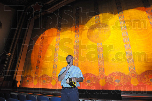 Tour guide: Roger Aleshire who along with his wife Kathy, owns the Indiana Theater was the guide for Saturday's tour of his business. About 30 people participated in the afternon tour. Behind him the handpainted fire curtain glows under spotlights.