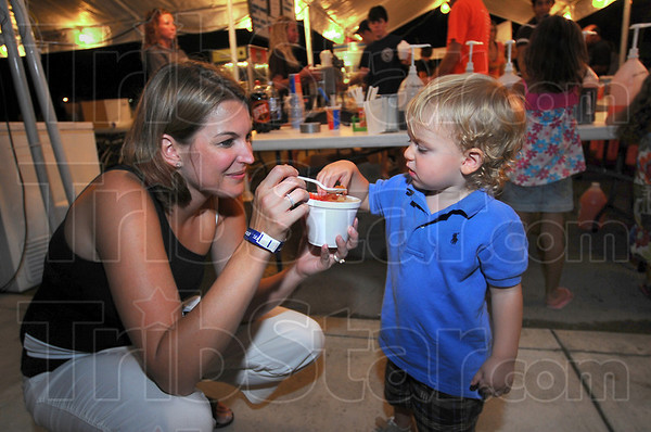 Sharing: Terran Williams shares her snow cone with her son Nicholas. The two were attending the St. Benedict Church street fair Friday evening.