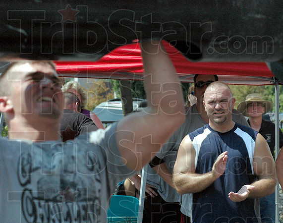 Good job: Tribune-Star reporter Brian Boyce (R) cheers for a competitor during the log press event at Saturday's Gladiator Challenge.
