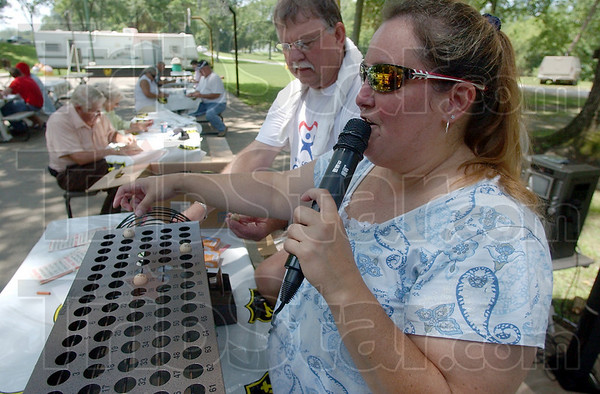 """Under the """"I"""": Susan Chervenko calls the Bingo numbers while Sam Chilton helps at the CASA open house at Forest Park Saturday."""