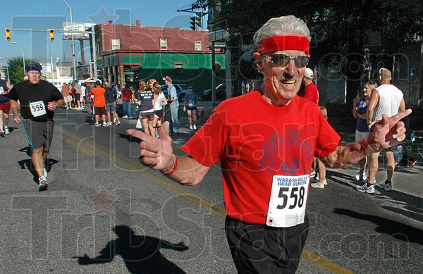 Granpa wins: Seventy-nine year old Bob Lemont heads for the finish line ahead of his son Bob Jr. during Saturday's Mayor's Cup Mile.