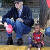 Young and old: WWII veteran Homer Bates and two-year-old Joshua Mason sit on the street Saturday morning watching the annual parade along Wabash Avenue.