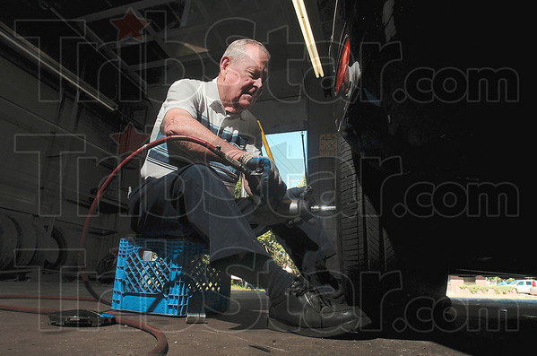 Tribune-Star/Joseph C. Garza<br /> Experienced hands: Joe Carney tightens the lug nuts on a customer's tire  June 24 at Carney's tire shop on Wabash Avenue.
