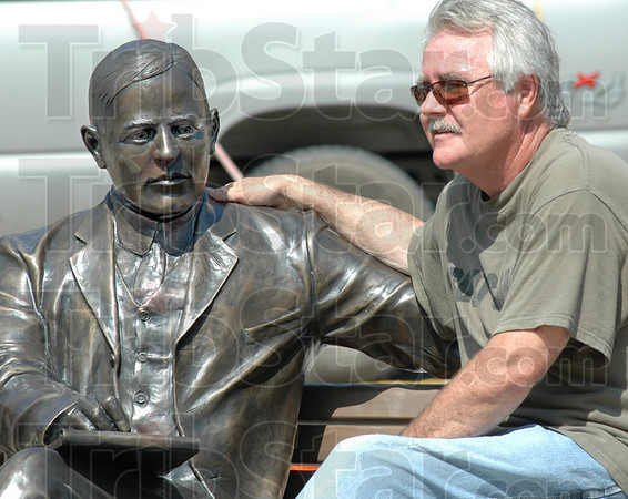 Relax with Max: Sculptor Bill Wolfe takes a break and sits with his Max Ehrmann sculpture as its being installed at 7th and Wabash Wednesday afternoon.