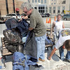 Cover-up: Sculptor Bill Wolfe covers his Max Ehrmann piece as Fred Vault and Richard Young of American Stone Fabricators install rods into the concrete base to anchor it into place.