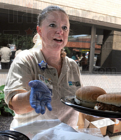 Server: Regional Hospital Registered Nurse Jennifer Adams serves BBQ sandwiches during Tuesday's Block Party event.