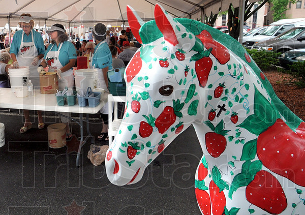 Fest detail: Detail of Festival equine with workers preparing strawberrys and ice cream for annual event Thursday afternoon.