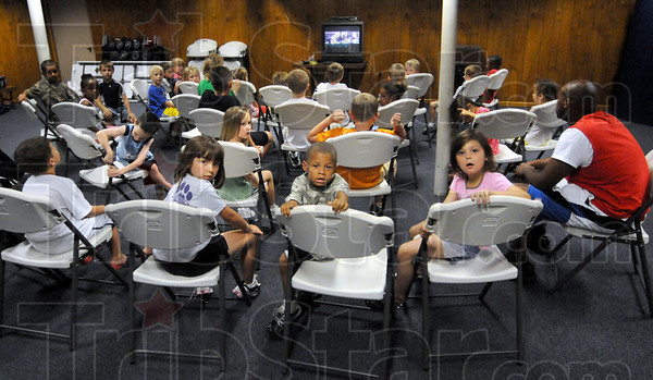 Program: A large group of kids watches a video at the Boy's and Girl's Club Thursday afternoon as part of a summer program.