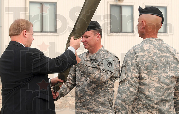 Tribune-Star/Joseph C. Garza<br /> The symbolic end: Lt. Col. William D. Hibner, Newport Chemical Depot commander, center, hands the encased flag of the depot to Conrad Whyne, Chemical Materials Agency director, as Sgt. Major Ricardo Soto stands at attention during the depot's deactivation ceremony Thursday.