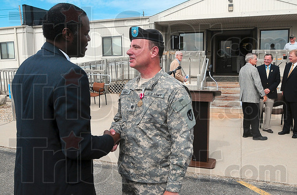 Tribune-Star/Joseph C. Garza<br /> Congrats from a former co-worker: Ronald Henton, a former vice president and general manager for the Mason & Hanger Corporation, congratulates Lt. Col. William D. Hibner for his years of service at the depot after the installation's deactivation ceremony Thursday.