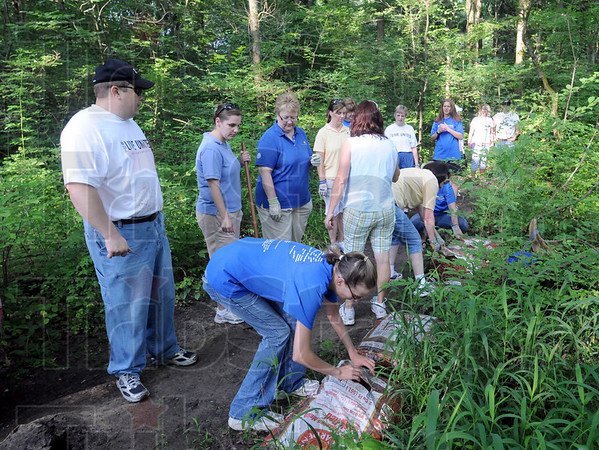 Day of Action: United Way volunteers work spreading mulch on the trails in Dobbs Park Friday morning.