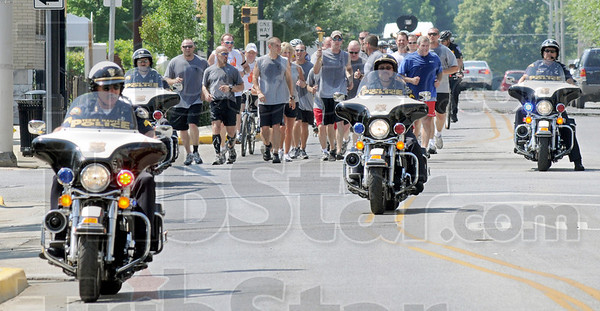 Torch arrival: A Terre Haute police motorcycle unit leads the way for the Special Olympics Torch Friday morning. The Torch was being carried by law enforcement and corrections officers as it enters the Indiana State University campus.